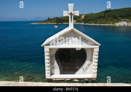 Roadside shrine overlooking bay at Kassiopi on the Greek Mediterranean island of Corfu Greece GR - Stock Photo