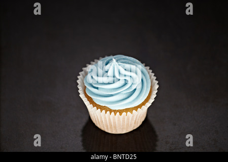 Cupcakes with blue icing on a black marble surface - Stock Photo