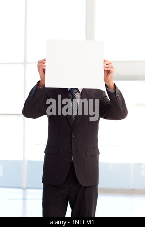 Man holding a big business card in front of his face - Stock Photo