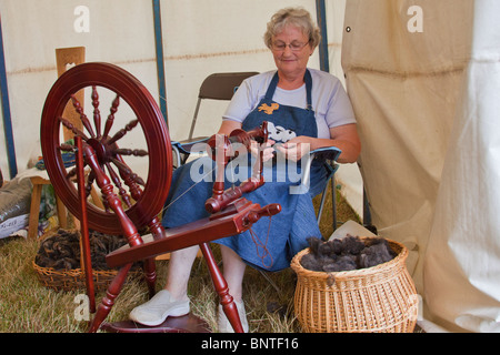 Old lady demonstrating a spinning wheel at Revesby Country Fair, Lincolnshire, England, wool spun to make balls - Stock Photo