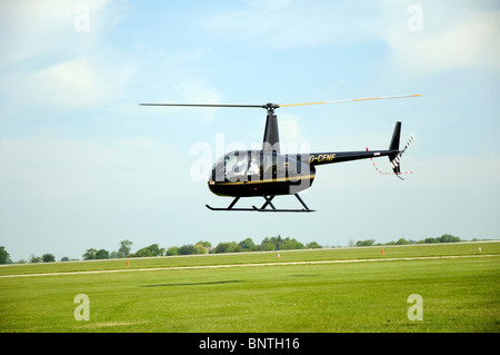 Robinson R44 helicopter just about to land at Sywell aerodrome - Stock Photo