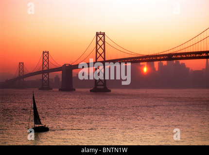 Sailboat passing Oakland Bay Bridge on San Francisco Bay with sunset peeking through silhouetted city skyline - Stock Photo