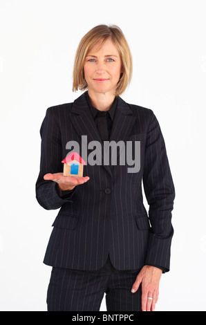 Mature businesswoman holding a house - Stock Photo