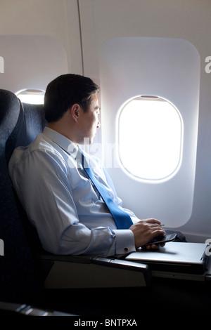 Businessman sitting on the plane - Stock Photo