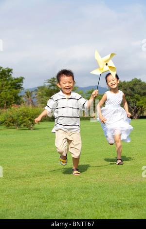 Children running with a pinwheel - Stock Photo