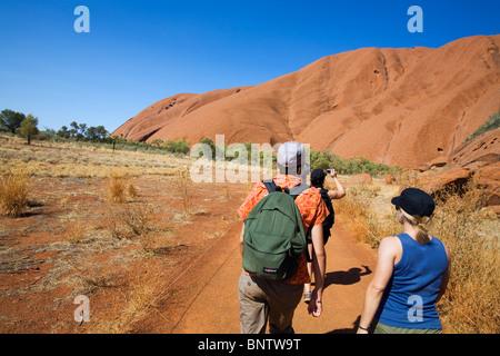 Hikers on the Uluru (Ayers Rock) Base Walk. Uluru-Kata Tjuta National Park, Northern Territory, AUSTRALIA. - Stock Photo
