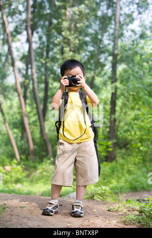 Little boy taking photos in nature - Stock Photo