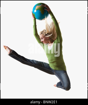 Woman jumping in air while holding globe - Stock Photo