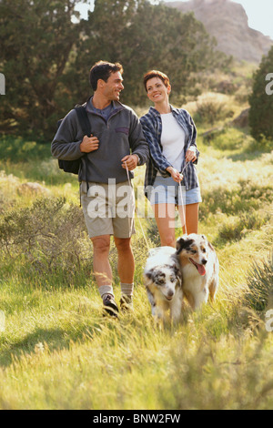 Couple walking their dogs in the countryside - Stock Photo