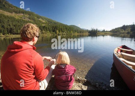 A father in his early forties shows a daughter how to fish in a lake on Vancouver Island, BC Canada - Stock Photo