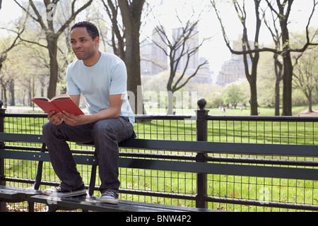Man sitting on bench reading book in Central Park - Stock Photo