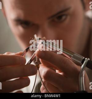 Man repairing fly fishing hook - Stock Photo