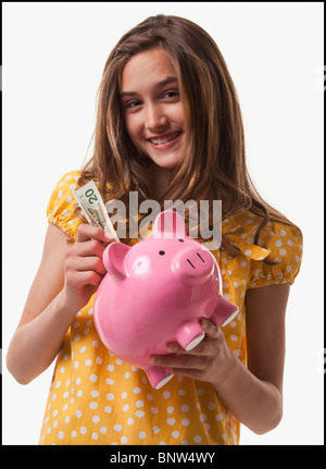 Teenage girl putting money in piggy bank - Stock Photo