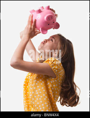 Teenage girl trying to get money out of piggy bank - Stock Photo