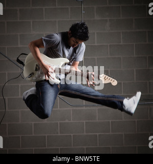 Man jumping in air while playing guitar - Stock Photo