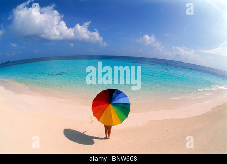 Woman standing alone in paradise with colorful umbrella on white sandy shore - Stock Photo