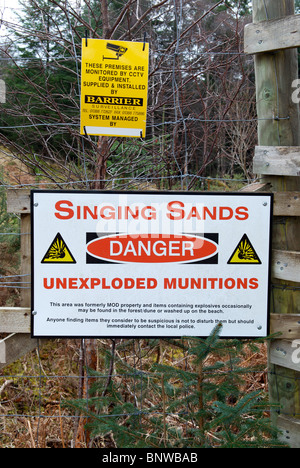 'Singing Sands Danger Unexploded Munitions' sign attached to a fence on a footpath, the Singing Sands, Ardnamurchan, - Stock Photo