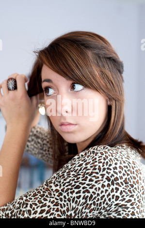 A pretty 16 year old girl fixes her hair before going shopping at the mall. USA. - Stock Photo