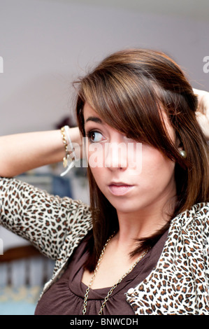A pretty 16 year old girl fixes her hair before going shopping at the mall. - Stock Photo