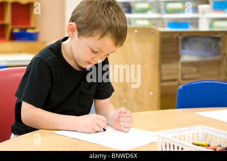 5 -year-old Mexican-American boy draws with crayons at pre-school - Stock Photo