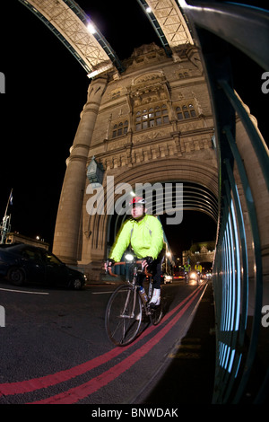 A cyclist in a reflective vest rides over Tower Bridge on the London Night Ride, London, United Kingdom - Stock Photo