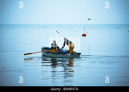 Fishermen rowing out to their fishing boat in the early morning, Swanage, Dorset, Uk - Stock Photo