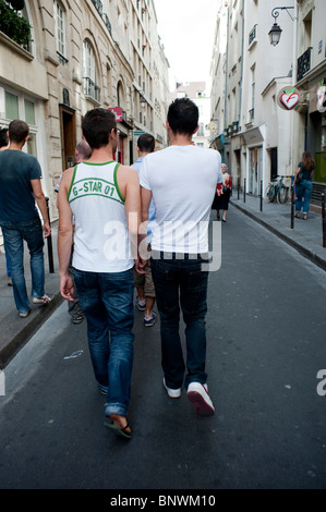 Young Adult, Gay Male Couple rear , Walking Down Street in the Marais District, Holding Hands, Paris, France - Stock Photo