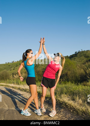 Two trail runners giving each other a high five - Stock Photo
