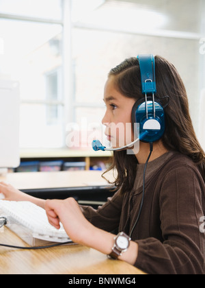 Elementary student wearing headphones in classroom - Stock Photo