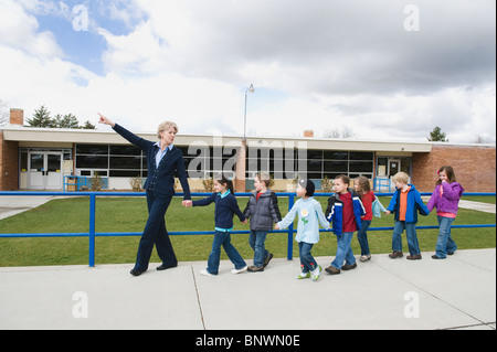 Elementary school students and teacher on a field trip - Stock Photo