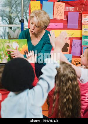 Elementary school teacher reading book to students - Stock Photo