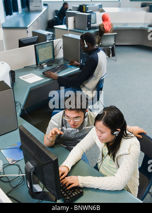 Adult students working on computers at a learning center - Stock Photo