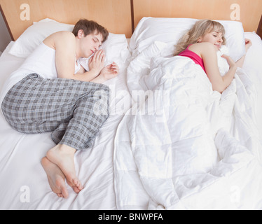 Couple sleeping in bed - Stock Photo