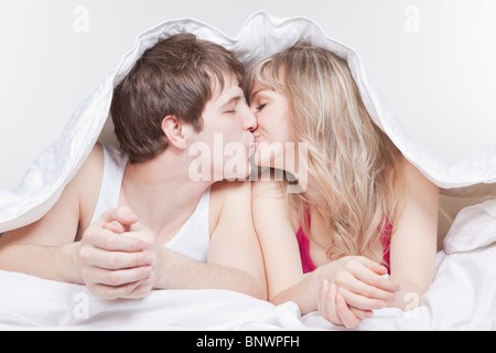 Couple kissing under the covers - Stock Photo