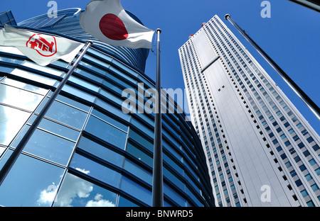 Low angle shot of Toyota Amlux showroom building, Japan flag & 'Sunshine City' skyscraper in Tokyo`s Ikebukuro district - Stock Photo