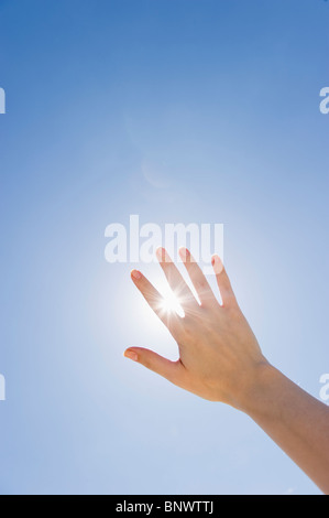 Hand held up in front of sunshine - Stock Photo