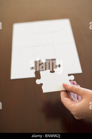 Hand putting last puzzle piece in puzzle - Stock Photo