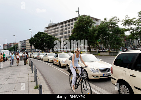 Woman Riding Bicycle past a Taxi Rank at Karlsplatz Stachus  Munich Germany - Stock Photo
