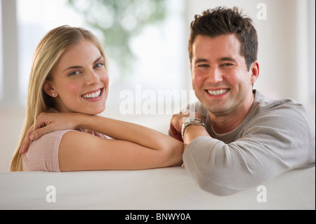 Happy couple relaxing on couch - Stock Photo