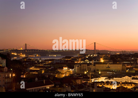 Dusk settles over the Portugese capital. The April 25 Suspension Bridge can be seen over the Tagus River in Lisbon, - Stock Photo