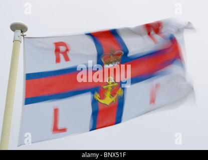 Royal National Lifeboat Institute flag flying in the wind showing motion blur - Stock Photo