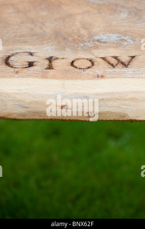 Wooden garden bench carved with the word 'Grow' at RHS Harlow Carr - Stock Photo