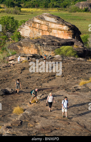 Tourists hike up the escarpment to the Nadab lookout at Ubirr. Kakadu National Park, Northern Territory, AUSTRALIA. - Stock Photo
