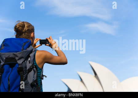 A backpacker photographs the Opera House in Sydney, New South Wales, AUSTRALIA. - Stock Photo