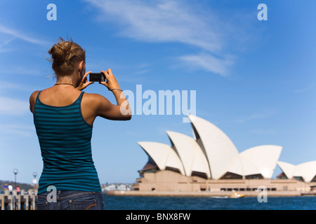 A woman photographs the Opera House in Sydney, New South Wales, AUSTRALIA. - Stock Photo