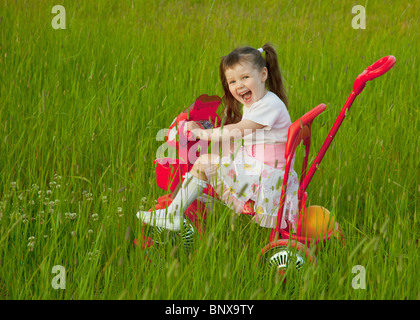 The cheerful little girl goes on a bicycle on a grass - Stock Photo