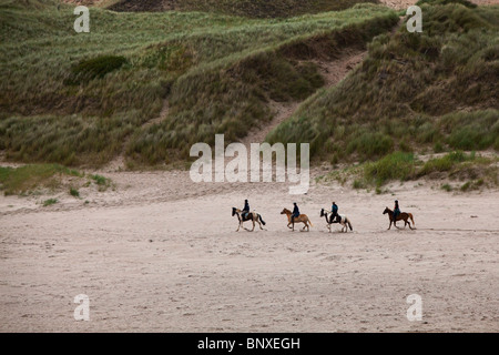 Four People Riding Horses On The Beach In County Donegal, Ireland - Stock Photo