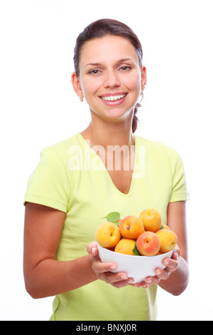 Smiling young woman keeping full bowl with apricots in her hands. Isolated over white. - Stock Photo