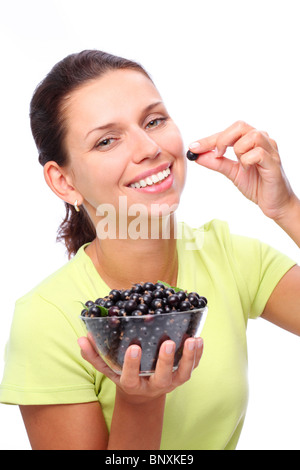 Smiling young woman with bowl full of black currants in her hands. - Stock Photo