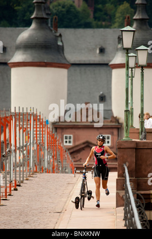 HEIDELBERG - AUGUST 1. The female winner cycling across the bridge. August the 1st, 2010 in Heidelberg, Germany. - Stock Photo